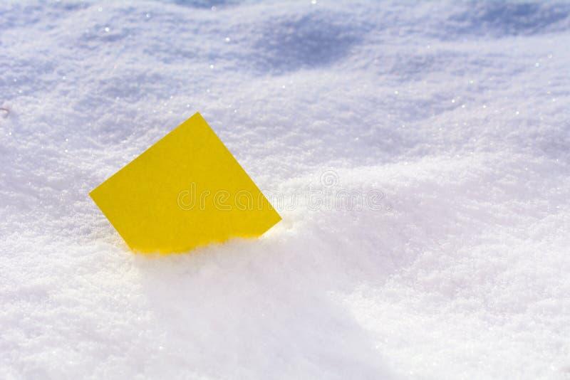 Etiqueta engomada amarilla en blanco en la nieve foto de archivo libre de regalías