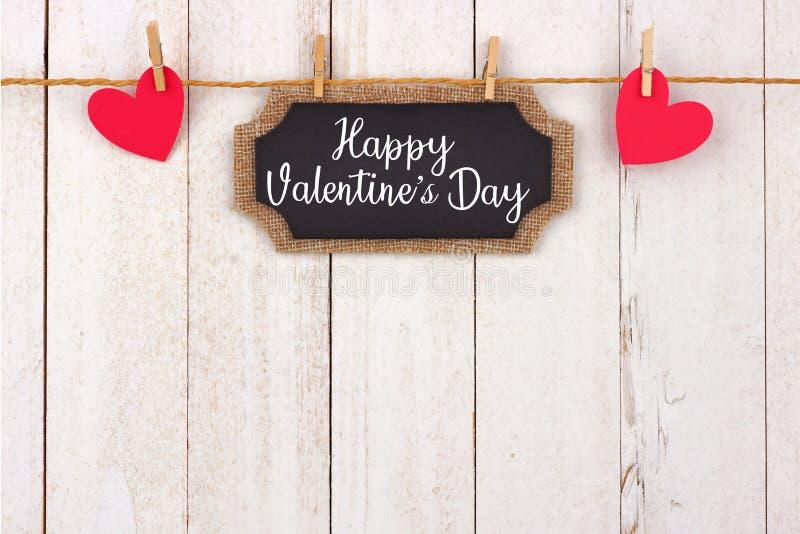Etiqueta feliz e corações do presente do quadro do dia de Valentim que penduram da linha, beira superior contra a madeira branca fotos de stock royalty free