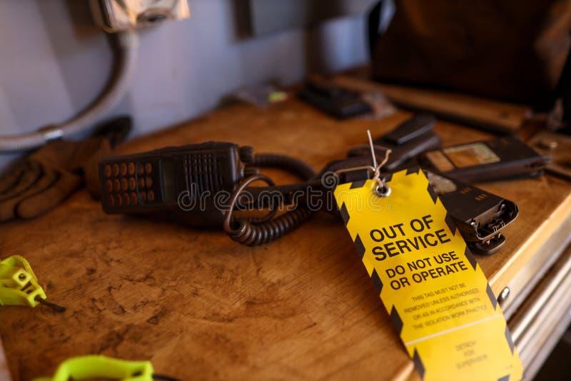 A etiqueta fora de serviço amarela unida em rádio em dois sentidos quebrado do defeito na tabela não se usa ou operação fotografia de stock royalty free
