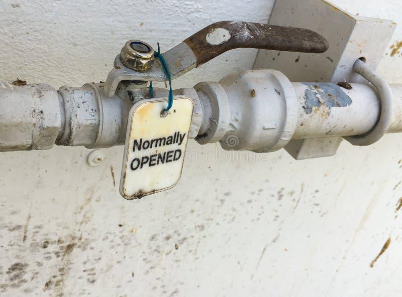 A etiqueta normalmente aberta está sendo pendurada na válvula da água foto de stock royalty free