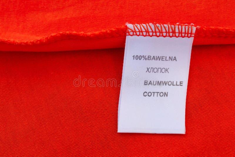 Etiqueta 100 por cento de algodão A inscrição em línguas diferentes: Russo, polonês, inglês, alemão fotografia de stock royalty free