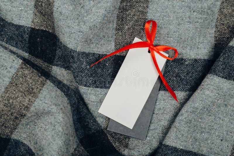Etiqueta rectangular en ropa moda, gente y concepto de las compras - cierre encima de la etiqueta del artículo de la ropa imágenes de archivo libres de regalías