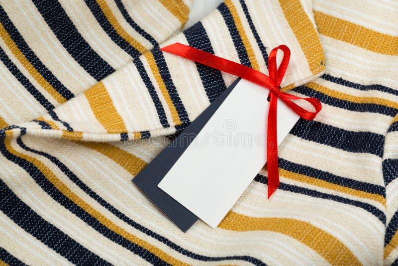 Etiqueta rectangular en ropa moda, gente y concepto de las compras - cierre encima de la etiqueta del artículo de la ropa imagen de archivo libre de regalías