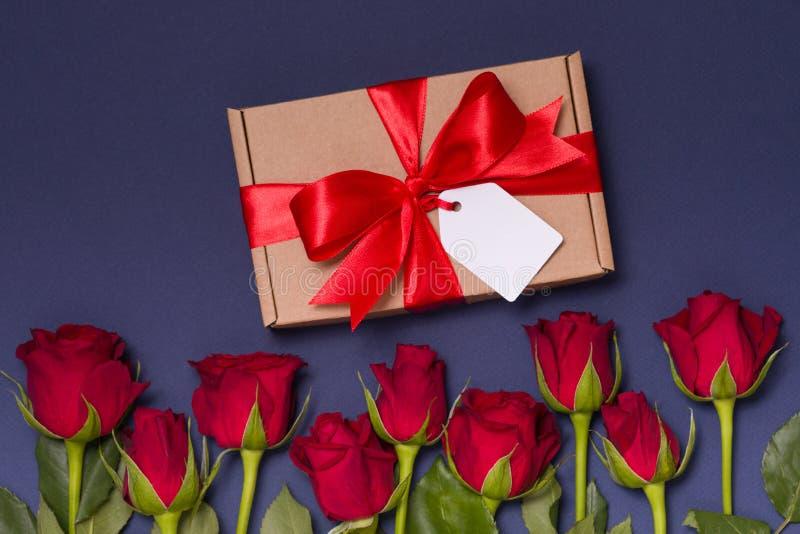 Etiqueta romântica da curva da fita do presente do dia de Valentim, rosas vermelhas do fundo azul sem emenda, espaço do texto da  fotos de stock