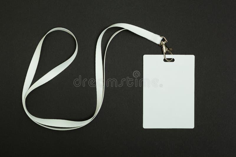 Etiqueta vazia da segurança com a faixa branca do pescoço isolada no fundo preto imagens de stock royalty free