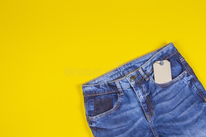 Etiqueta vazia do preço da etiqueta com calças de ganga no fundo amarelo foto de stock royalty free