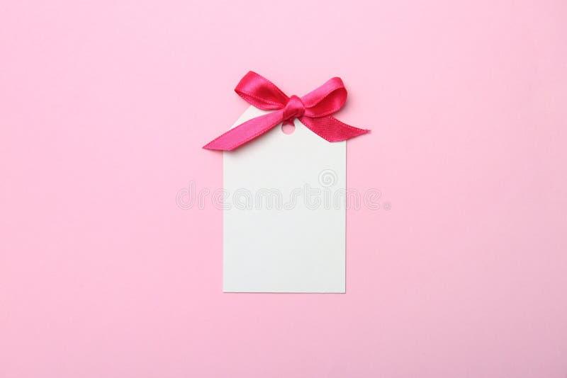 Etiqueta vazia do presente com a fita do cetim no fundo da cor fotografia de stock royalty free