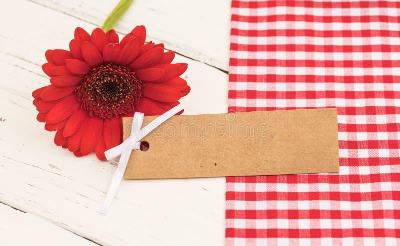 Etiqueta vazia do presente com a flor vermelha com espaço da cópia para o texto fotos de stock