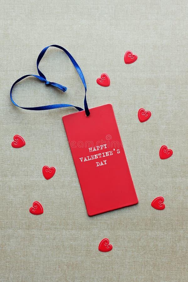 Etiqueta vermelha do presente com DIA de VALENTIM FELIZ da máquina de escrever e o ribbo azul fotos de stock royalty free