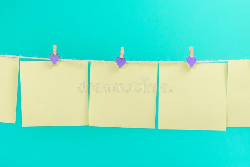 Etiquetas amarelas na corda com os pregadores de roupa isolados no fundo azul fotos de stock