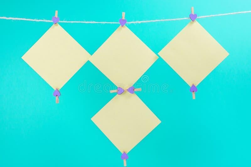 Etiquetas amarelas na corda com os pregadores de roupa isolados no fundo azul fotografia de stock royalty free