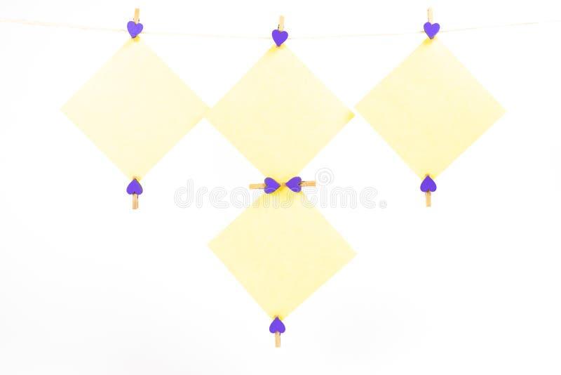 Etiquetas amarelas na corda com os pregadores de roupa isolados no fundo branco fotos de stock