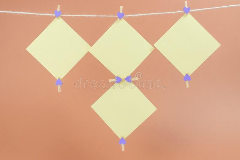 Etiquetas amarelas na corda com os pregadores de roupa isolados no fundo marrom imagem de stock royalty free
