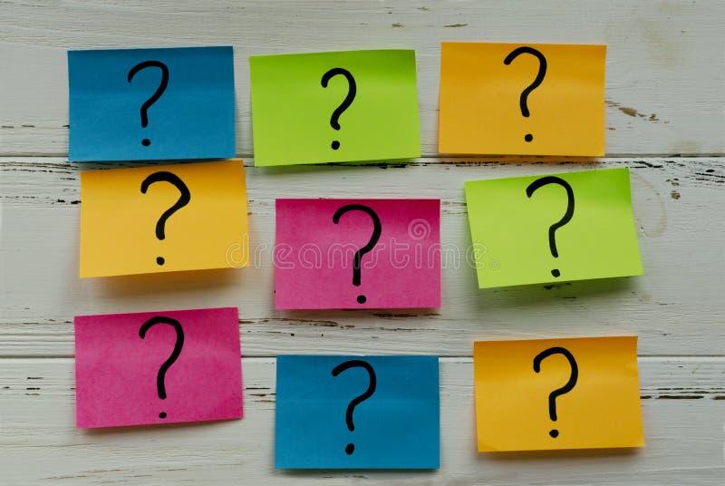 Etiquetas coloridas com pontos de interrogação na tabela de madeira do vintage branco imagem de stock royalty free