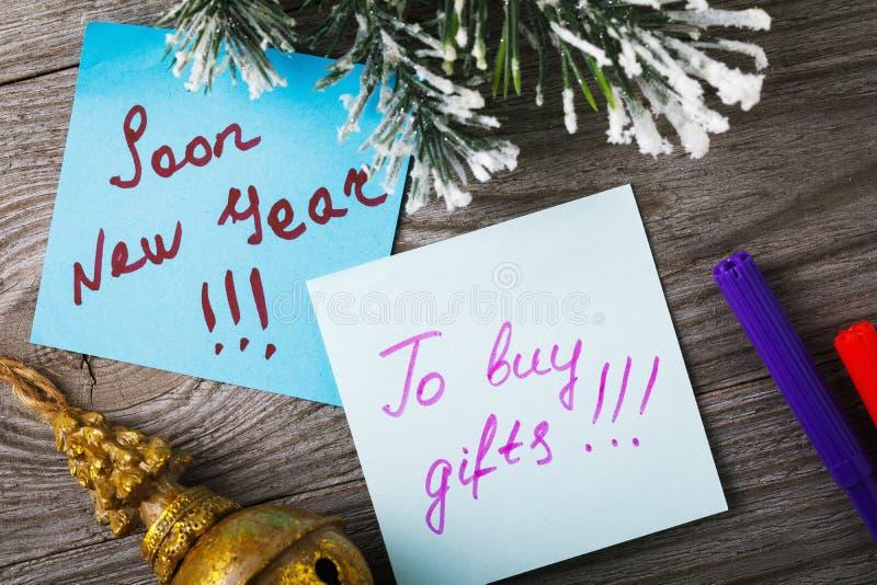 Etiquetas com notas sobre o ano novo em um fundo de madeira fotografia de stock