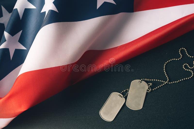 Etiquetas da bandeira americana e dos soldados no fundo de madeira Conceito do dia de veteranos imagem de stock royalty free