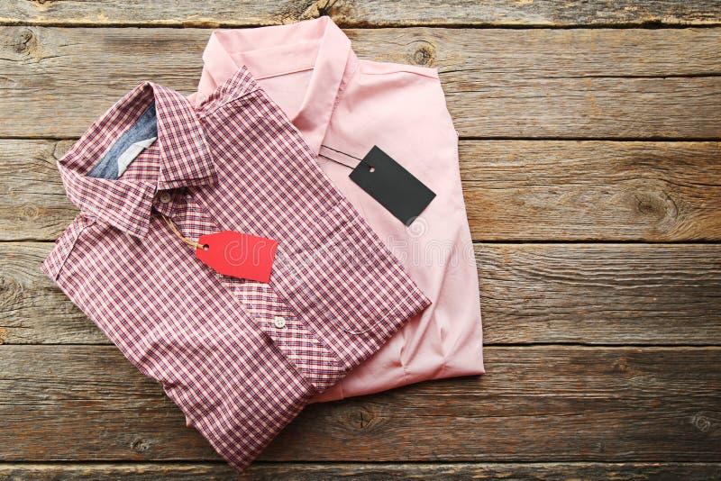 Etiquetas da venda com camisas novas imagens de stock