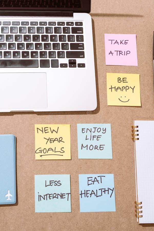 Etiquetas de papel coloridas com estratégia empresarial e portátil no tabletop imagens de stock