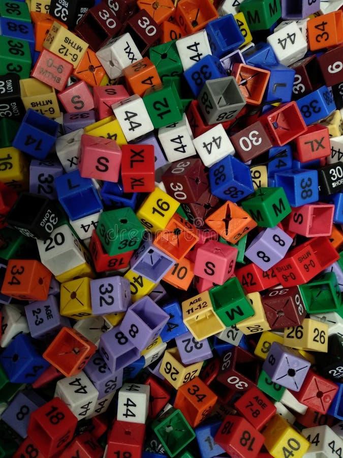 Etiquetas de tamaño de ropa Comcept de variedad colorida fotos de archivo
