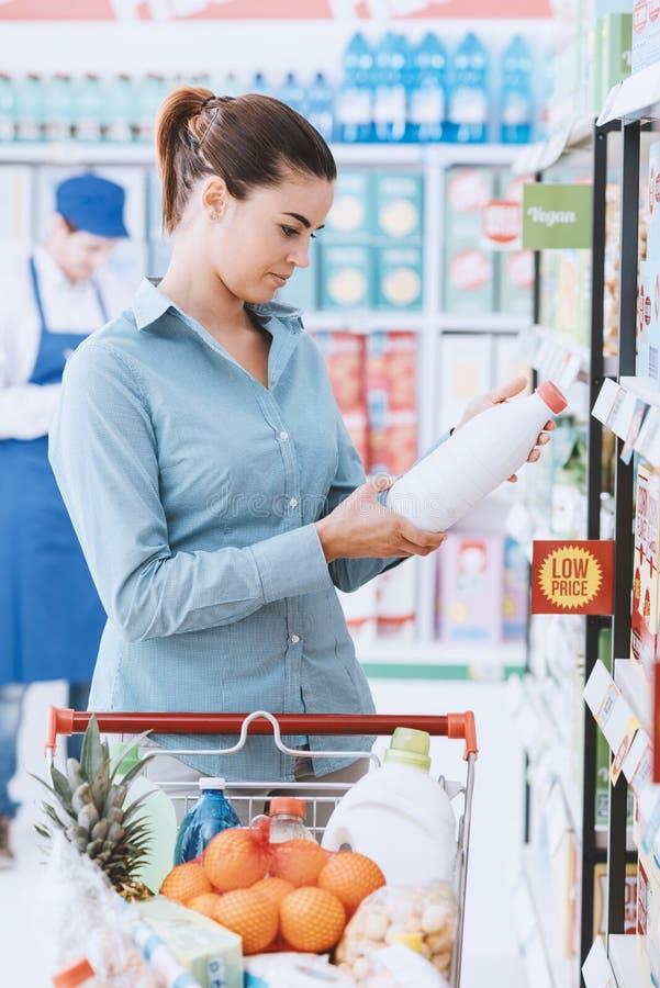 Etiquetas do alimento da leitura da mulher fotografia de stock