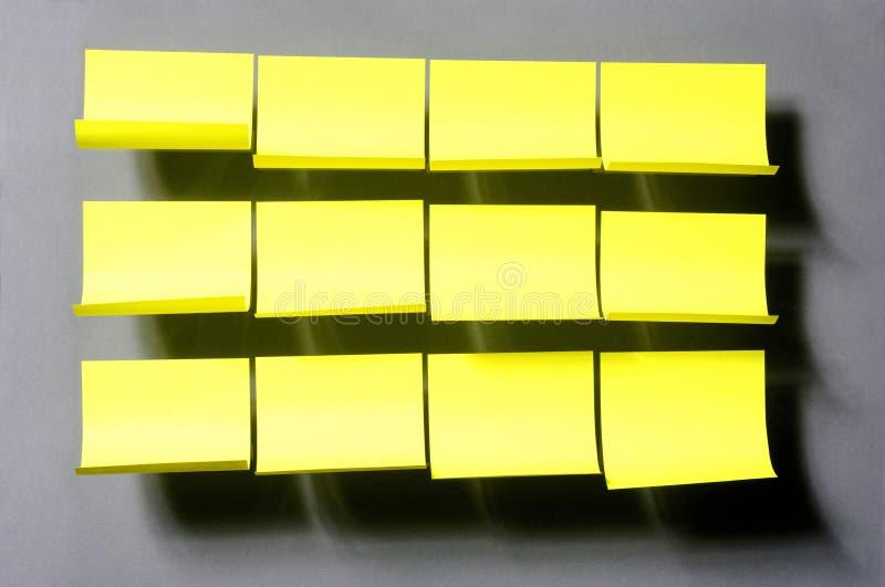 Etiquetas engomadas amarillas en el fondo gris imagenes de archivo