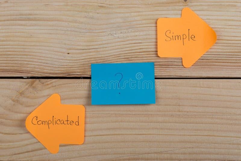etiquetas engomadas anaranjadas de la opción de la vida bajo la forma de flechas del índice con el texto complicado y simple en f foto de archivo libre de regalías