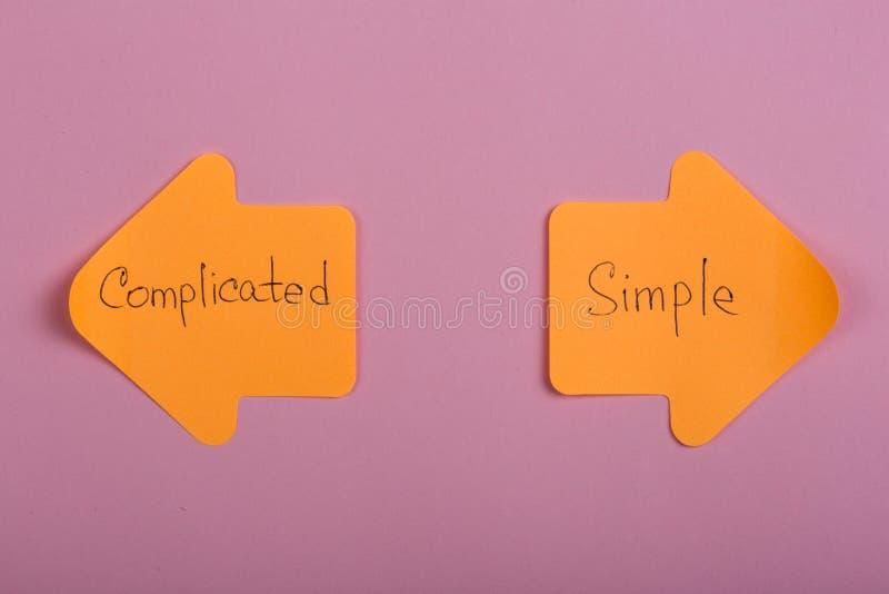 etiquetas engomadas anaranjadas de la opción de la vida bajo la forma de flechas del índice con el texto complicado y simple en f fotografía de archivo