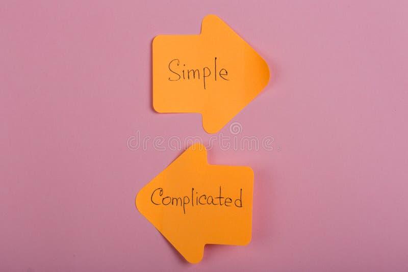etiquetas engomadas anaranjadas de la opción de la vida bajo la forma de flechas del índice con el texto complicado y simple en f fotografía de archivo libre de regalías
