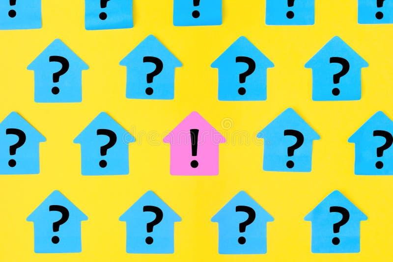 Etiquetas engomadas bajo la forma de casas en un fondo amarillo brillante En notas pegajosas azules un signo de interrogación fue imágenes de archivo libres de regalías