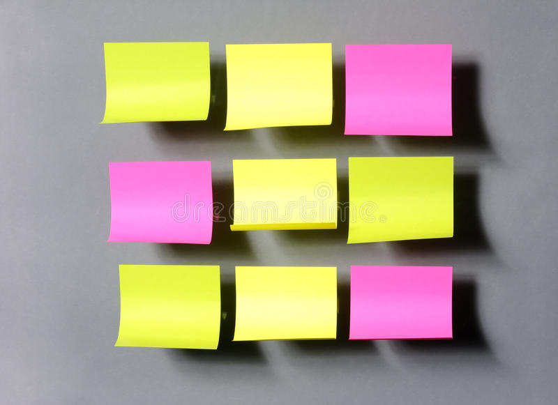 Etiquetas engomadas coloridas en el fondo gris imagen de archivo