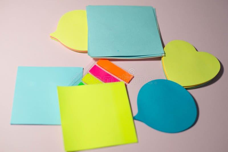 Etiquetas engomadas de papel en un fondo rosado imagen de archivo