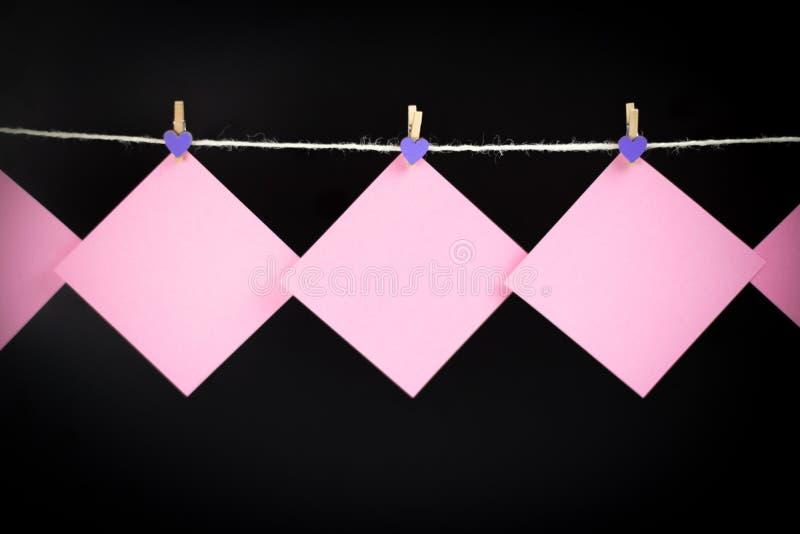 Etiquetas engomadas rosadas en cuerda para tender la ropa con las pinzas aisladas en fondo negro imagenes de archivo