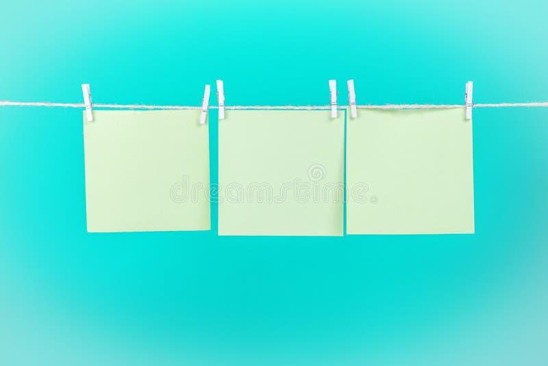 Etiquetas engomadas verdes en cuerda para tender la ropa con las pinzas aisladas en fondo azul imagenes de archivo