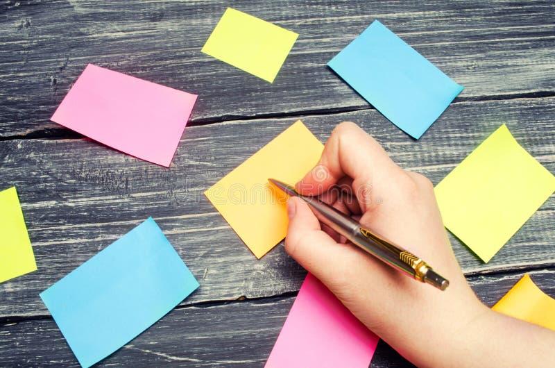 Etiquetas pegajosas para notas em um fundo de madeira preto gestão de tempo, ideia nova criativa Memória má lembrete foto de stock