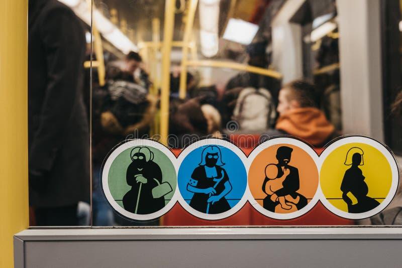 Etiquetas que pedem para dar acima o assento às concessões dentro do transporte do tubo em Viena, Áustria fotos de stock