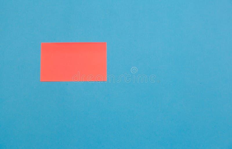 Etiquetas vazias cor-de-rosa do quadrado do papel no fundo azul, espaço da cópia fotos de stock