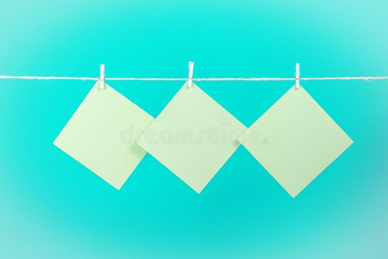 Etiquetas verdes na corda com os pregadores de roupa isolados no fundo azul foto de stock royalty free