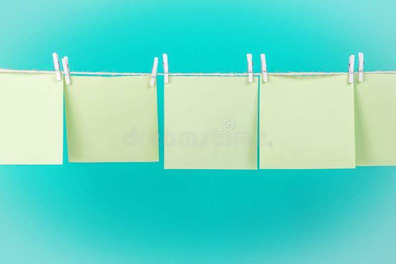 Etiquetas verdes na corda com os pregadores de roupa isolados no fundo azul fotos de stock royalty free