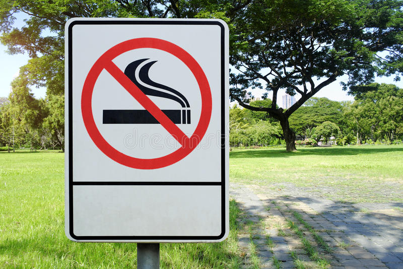 Etiquete o metal não fumadores assinam dentro o parque foto de stock
