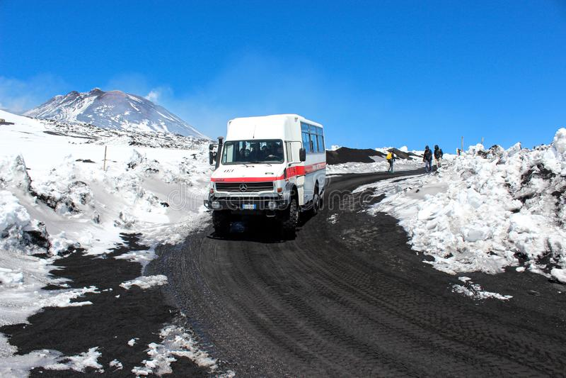 Etna,西西里岛,意大利- 2019年4月9日:驾驶游人的旅游吉普或公共汽车到Etna火山和后面上面  在火山的雪 免版税库存照片