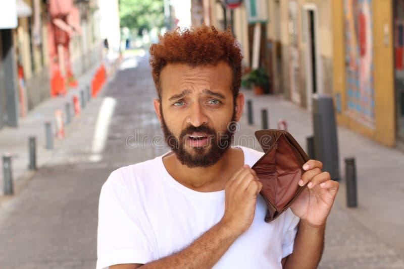 Etnico ha rotto il tipo con il portafoglio vuoto all'aperto fotografia stock
