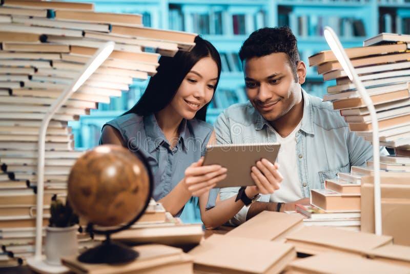 Etniczna azjatykcia dziewczyna i indyjski mieszany biegowy facet otaczający książkami w bibliotece Ucznie używają pastylkę fotografia stock