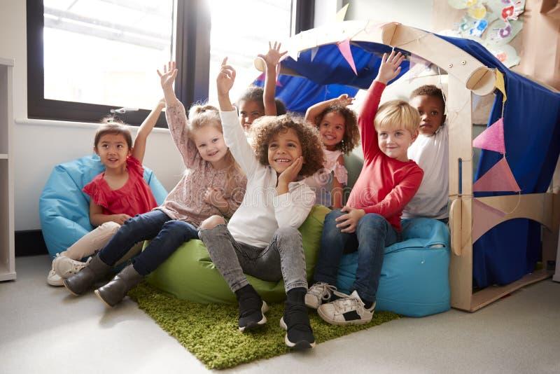 Etniczna grupa dziecięcy dzieci w wieku szkolnym siedzi na bobowych torbach w wygodnym kącie sala lekcyjna, podnosi ich ręki zdjęcie stock