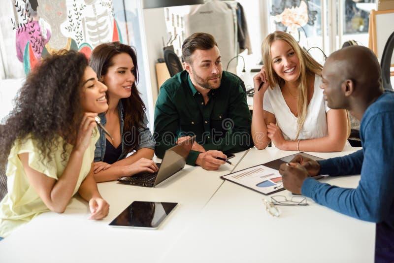 Etniczna grupa młodzi ludzie studiuje wpólnie na białym de zdjęcie royalty free