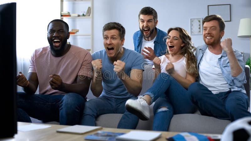 Etniczna grupa przyjaciele ogląda mecz futbolowego w domu, świętuje cel obraz stock