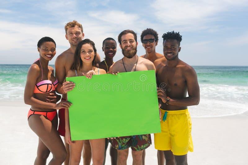 Etniczna grupa przyjaciele trzyma pustego zielonego plakat przy plażą na słonecznym dniu zdjęcia stock