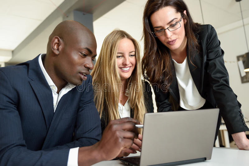 Etniczna grupa trzy biznesmena spotyka w nowożytnym o zdjęcie stock
