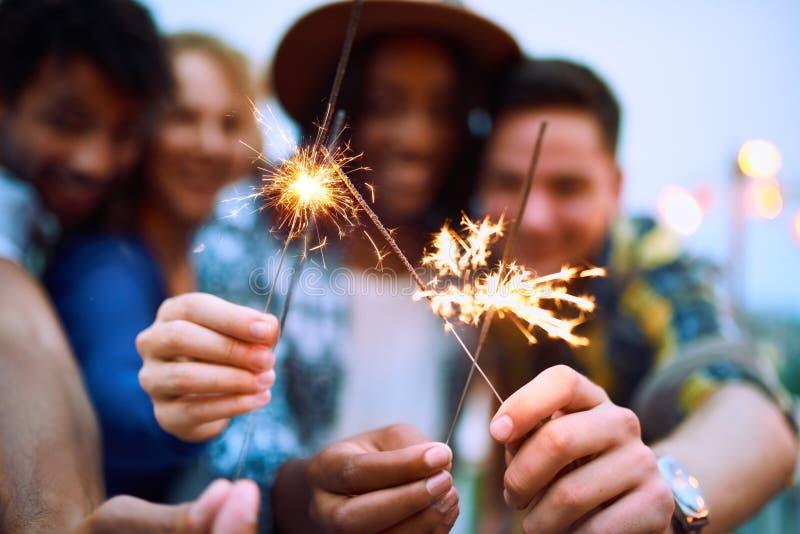 Etniczna millenial grupa friendsfolding sparklers na dachu terrasse przy zmierzchem obraz stock