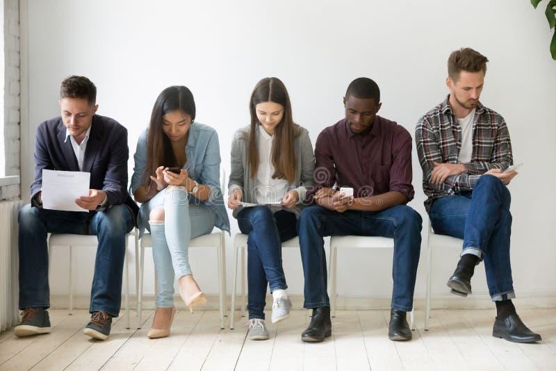 Etniczni millennial ludzie czekają w kolejki narządzaniu dla pracy mnie zdjęcia stock