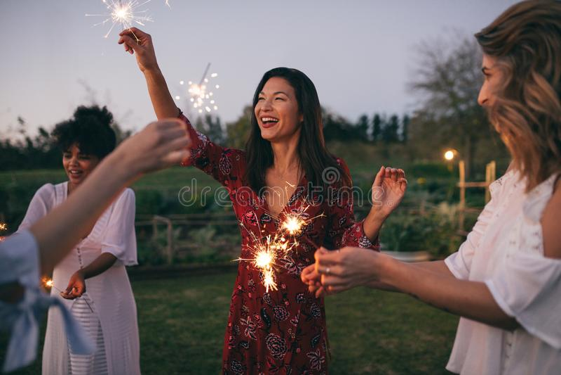 Etniczni przyjaciele cieszy się przyjęcia z sparklers obrazy stock